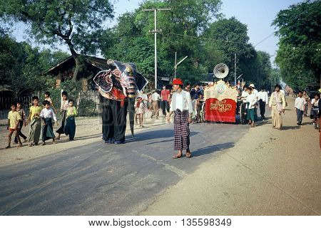 PAGAN / MYANMAR - CIRCA 1987: Men in an elephant suit participate in a Buddhist parade in Pagan during a holiday.