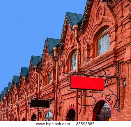 Sign board. Vintage shopping arcade - architecture background. Exterior architecture of old shopping arcades of the 19th century. Russian stone architecture of the 19th century. Old brick building.