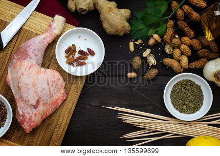 raw chicken leg with ingredients on a dark wooden table view from above cooking Asian meat skewers with satay peanut sauce