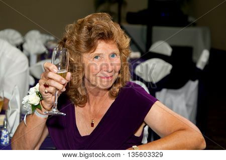 A mother of a bride holds her champagne glass up to toast her daughter and new son at a wedding reception.