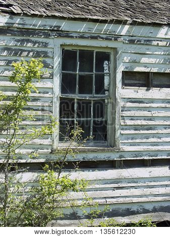 A beat up old lonely house with chipping paint.