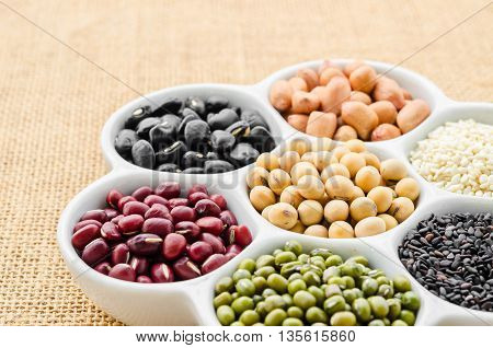collection set of beans legumes peas lentils on ceramic bowl on sack background