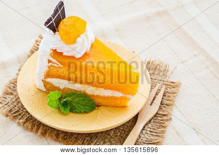 orange cake with chocolate and wipping cream topping on tablecloth.