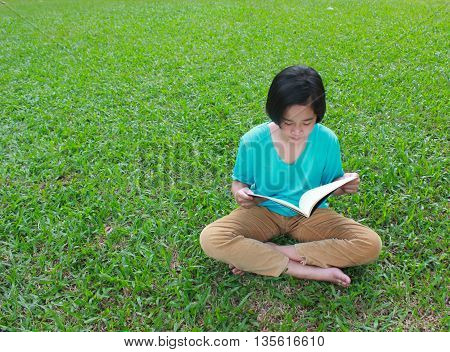 Young girl reading in the park, spring time.
