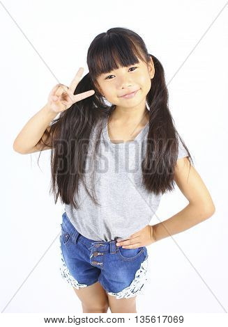 Portrait of young cute girl posting with two fingers isolated on white