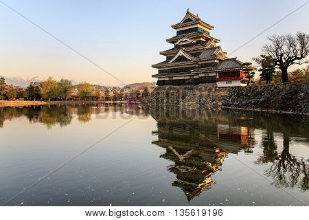 Reflection of Matsumoto castle with warm light in morning with cherry blossom and Japan alps background