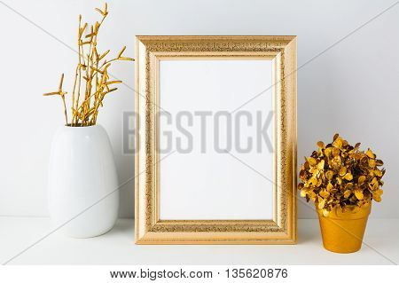 Gold frame mockup with white vase and golden flowerpot. Empty gold frame mockup for design presentation. Portrait or poster gold frame mockup.