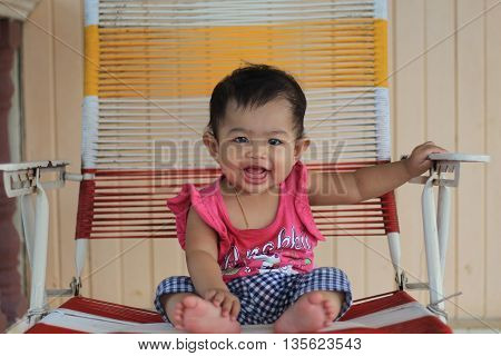 Infant seating on chair with happy face