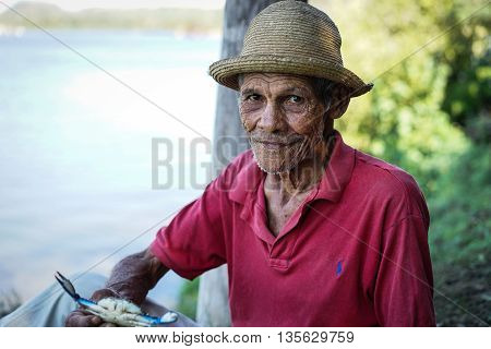 Cayo Granma Santiago De Cuba. Cuba - January 11 2016: old Cuban man who has caught crabs and displays the day's catch. He wears the straw hat as protection against sun rays and a red polo shirt. He is unshaven and his face is wrinkled
