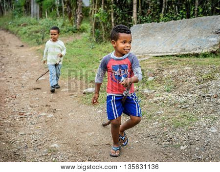 Trinidad Cuba - January 14 2016: Two adorable little boys playing with their homemade stick horses hobbyhorse in a poor district near Trinidad