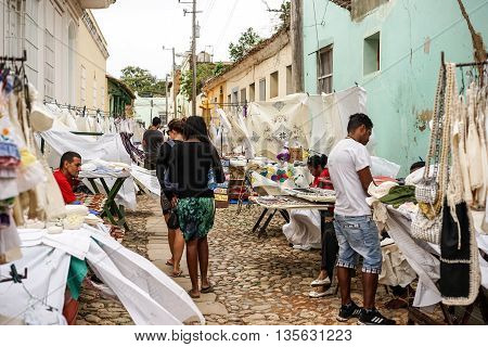 Trinidad Cuba - January 14 2016: Typical scene of one of streets in the center of Trinidad Cuba - colonial architecture people walking around street market selling souvenirs to tourists