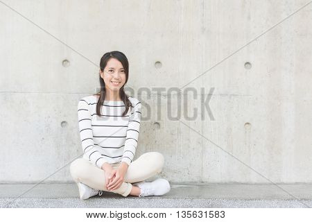 asian young woman sit with copyspace on wall