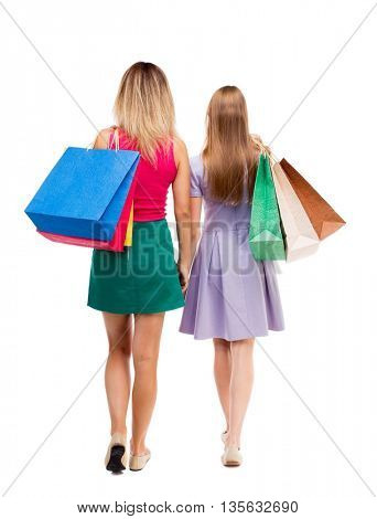 back view of  two walking women  with shopping bags. Isolated over white background. Two pretty girls in fancy dresses go ahead with shopping bags thrown over his shoulders.