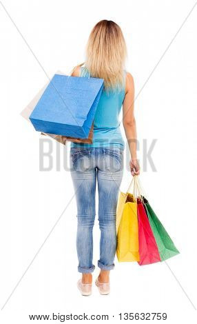 back view of woman with shopping bags . Isolated over white background. The girl in jeans and a blue shirt is throwing his purchases on his shoulder.