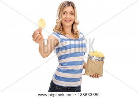 Cheerful woman holding a bag of potato chips in one hand and a single chip in the other isolated on white background