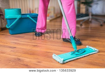 Woman Is Mopping Wooden Floor With Mop.