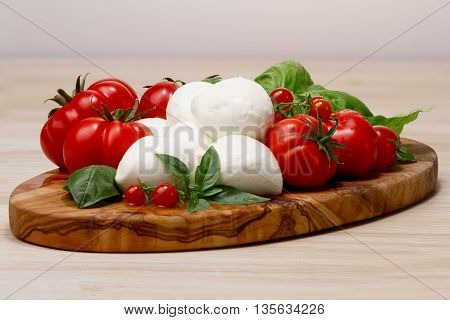 Mozzarella, Heirloom Tomatoes, Basil Leaves On A Wooden Serving Plate