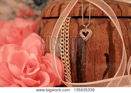 Jewellery box with a heart necklace and pink rose.