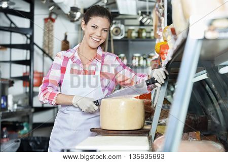 Smiling Young Saleswoman Slicing Cheese With Knife In Shop