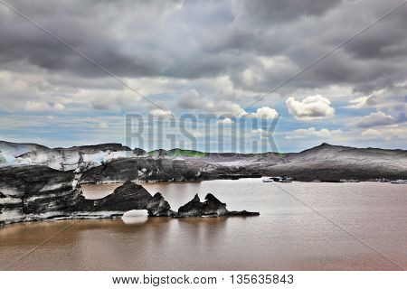 Ice covered with volcanic ash. Mirror Lake, formed as a result of thawing of a glacier Vatnajokull glacier spurs. Iceland in July. Skaftafell National Park