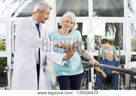 Doctor Showing Reports On Computer To Woman In Fitness Center