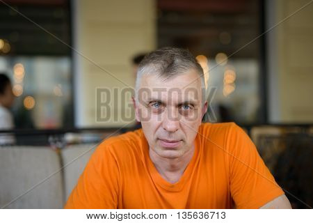 Matured man staring at camera sitting in cafeteria or restaurant. Front cropped shot