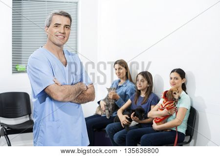 Confident Nurse Standing While Pet Owner Waiting In Clinic