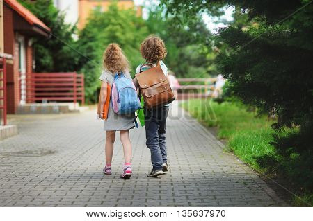 Two young students go to school hand in hand. Children behind shoulders have satchels. These are pupils of elementary school.