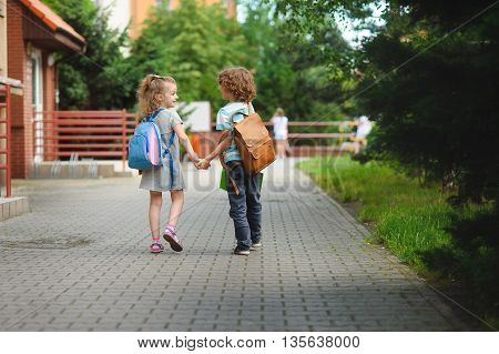 Back to school. Two young students go to school hand in hand. They about something briskly talk. Behind the back of everyone satchel.