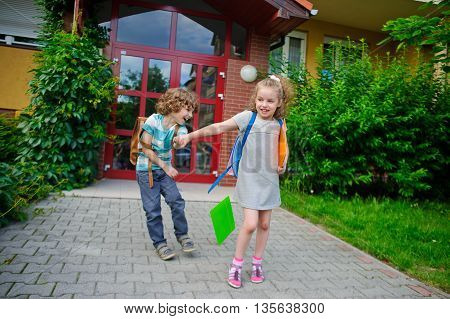 Two pupils of elementary school on a schoolyard. Boy and girl. The boy pulls the schoolmate by a hand. At him the folder has fallen. To children it is cheerful. They laugh.