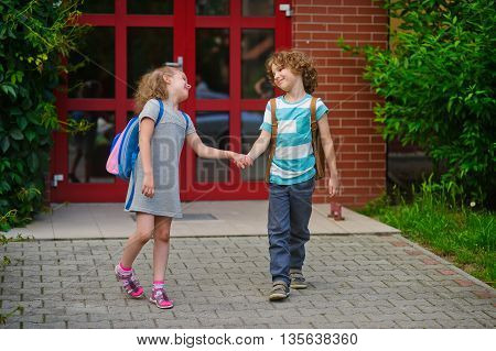 Little school students go on a schoolyard holding hands. Children with a smile look at each other. Boy and girl. Schoolmates.