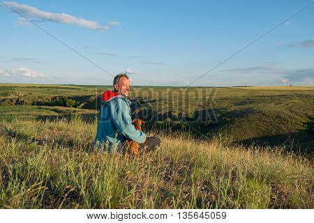Joyful hiker man sits with a dog in the prairie and looking into the distance. Sunset in a prairie desert. Azov steppes Ukraine.