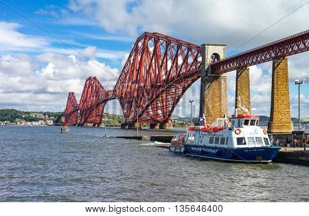 South Queenferry Scotland - July 29 2012: Lothian area the Forth Rail Bridge with a tour boat moored