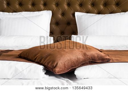 Brown cushion lying on a throw rug over a white duvet on a stylish double bed with upholstered brown headboard close up view