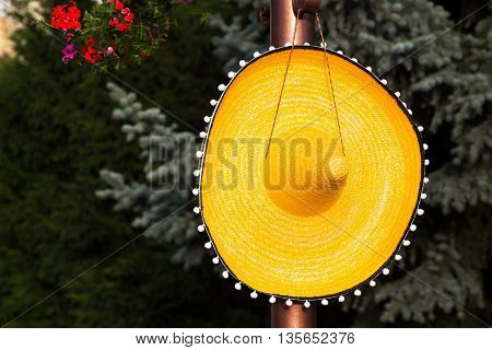 Large wide brimmed straw sombrero hanging on a peg on a wooden pole conceptual of travel to Mexico or Mexican fashion against a backdrop of greenery with copy space