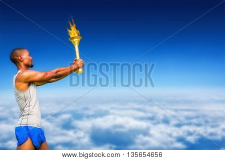 Profile view of sportsman holding a cup against blue sky over clouds at high altitude