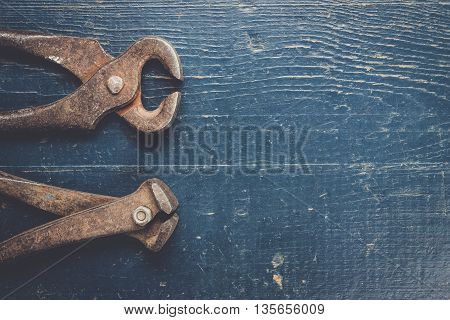 old rusty tongs on blue wooden background