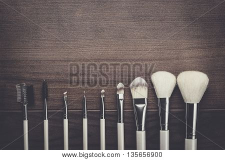 white make-up brushes on brown wooden background