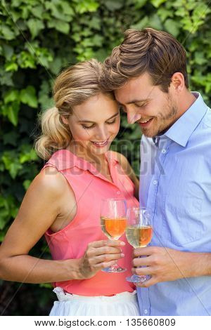Happy romantic couple toasting wineglasses at front yard
