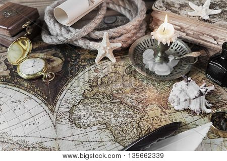 Burning candle scrolls of paper pen ink pocket watch and the ship's rope located on the background of old map
