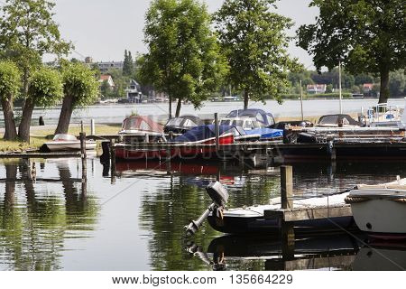 Boats moored in a small harbor in Rotterdam in the Netherlands. Selective focus on outboard motor.