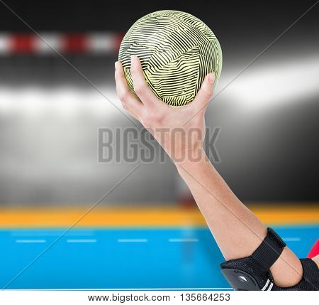 Female athlete with elbow pad holding handball against digital image of handball goal