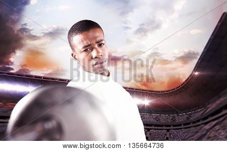 Swordsman practicing with fencing sword against composite image of stadium against cloudy sky