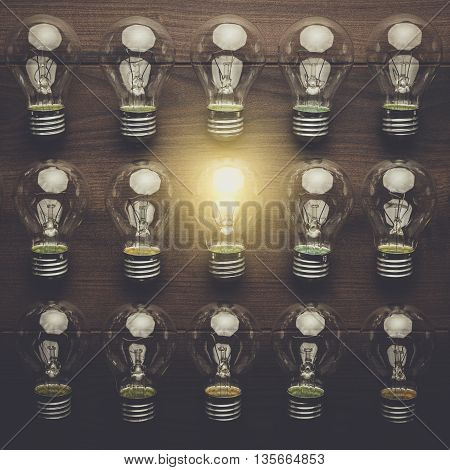 glowing bulb uniqueness concept on brown woodentable