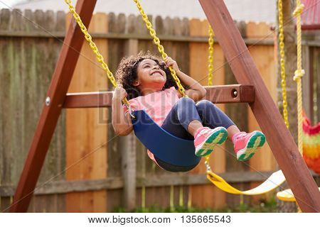 Kid toddler girl swinging on a playground swing in the backyard latin ethnicity