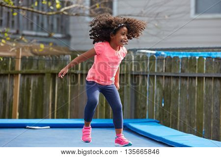Kid toddler girl jumping on a trampoline playground in the backyard latin ethnicity