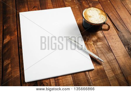 Blank branding template on vintage wooden table background. Photo of blank letterhead coffee cup and pen. Blank stationery set. Blank mock-up for your design.