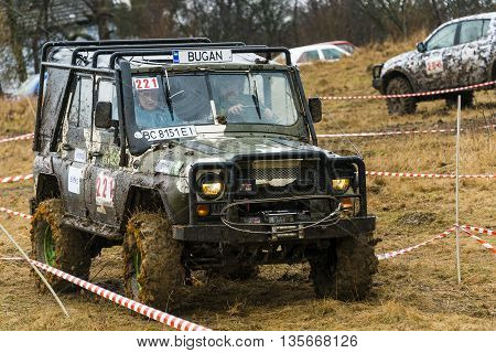 Lviv Ukraine - February 21 2016: Off-road vehicle UAZ (No. 221) overcomes the track on landfill near the city Lviv.
