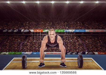 Bodybuilder lifting heavy barbell weights against view of a stadium