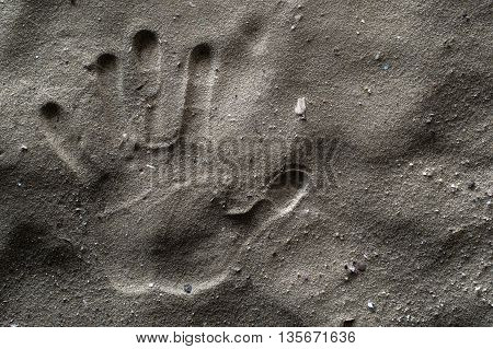 A Hand Print on Dirty Sand. Left Hand. Hdr picture.